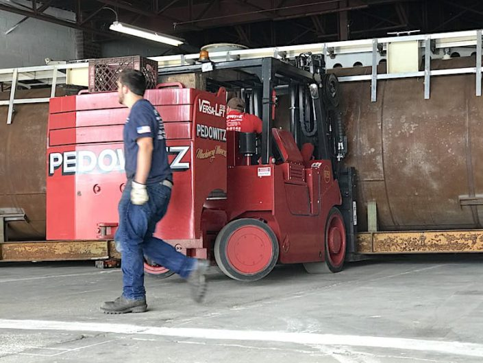 worker wit heavy lift forklift and hull