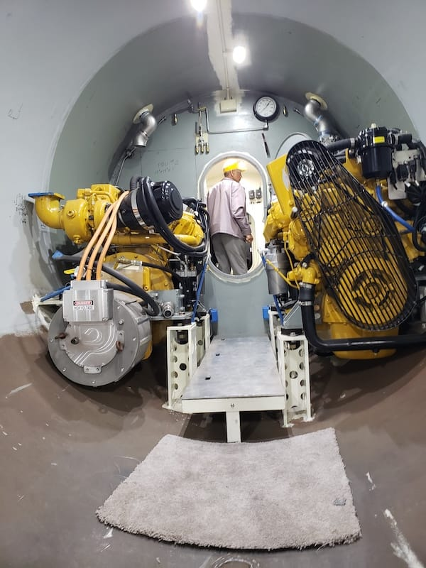United States Submarine Veterans member from Westport, CT examining pilot compartment. In foreground is engine compartment of private submarine to be christened SeaHawk.